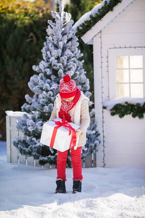 Nice weinig jongen met rode hoed en groene glazen vindt een groot heden dichtbij de Kerstboom royalty-vrije stock foto's