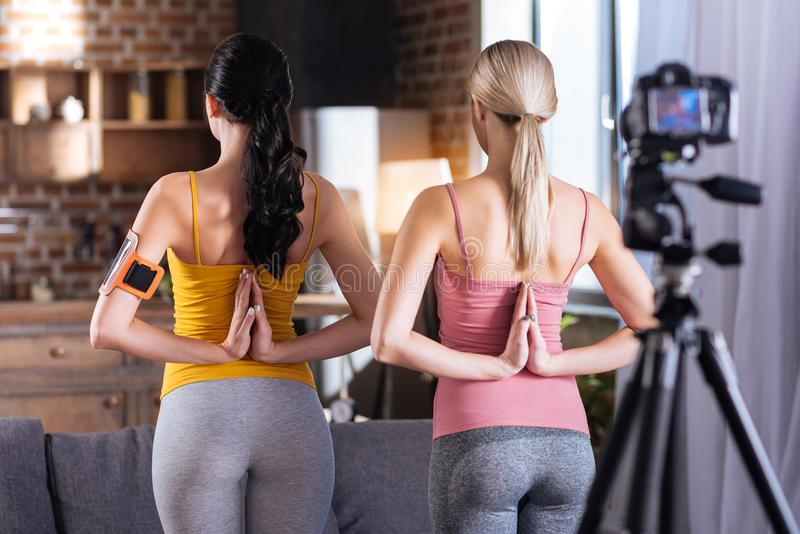 Nice well built women holding hands behind their backs. Yoga pose. Nice positive well built women tuning their back to the camera and putting their hands royalty free stock photography