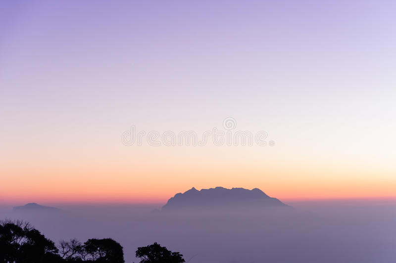 Nice white fog at the mountain in the morning with sunrises light and tree silhouette and small mountain in background royalty free stock photography