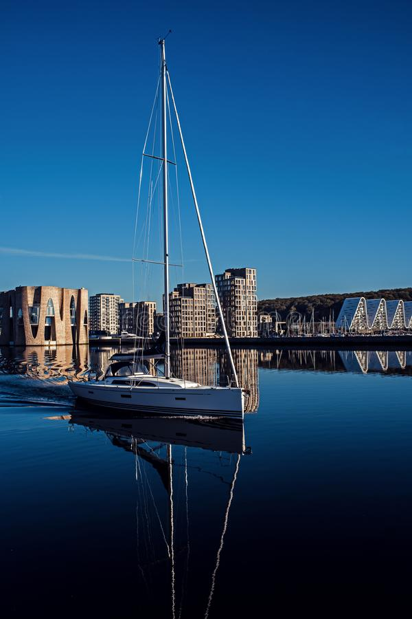 Nice white sailing yacht.Landscape of buildings near the pier. Yacht on the background of new buildings. stock photography