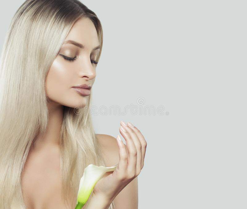 Nice Woman with Clean Fresh Skin, Healthy Blonde Hair. And Lily Flowers in her Hands. Facial Treatment, Cosmetology, Beauty, Skin Care and Spa stock photography