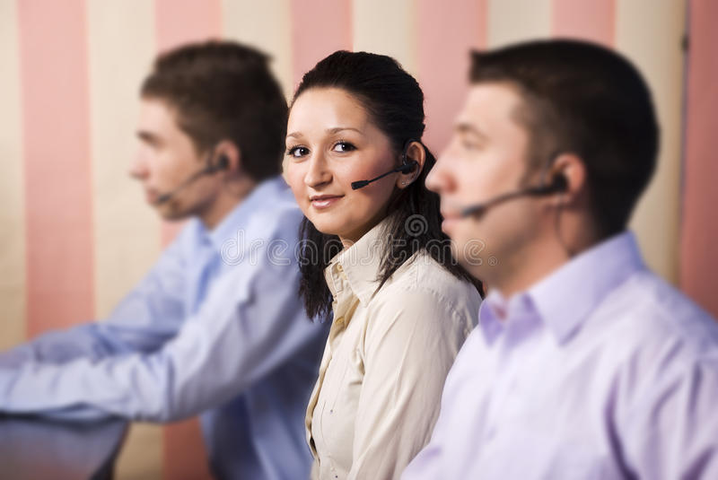 Nice woman customer service and her team. Focus on nice young woman customer service representative looking and smiling at you in the middle of two men team in stock images