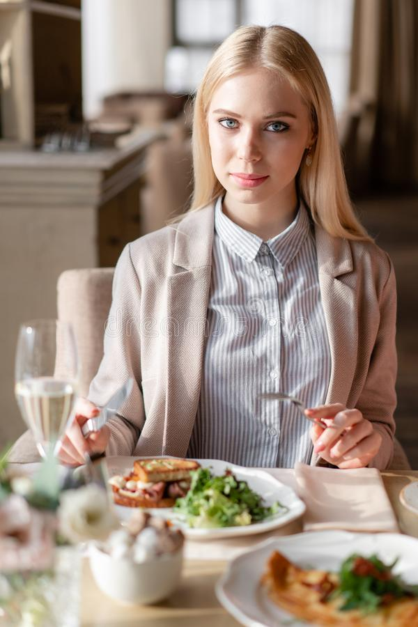 Nice woman eat breakfast in cafe. Portrait of young charming female drinking coffee and toasted sandwich in modern royalty free stock images