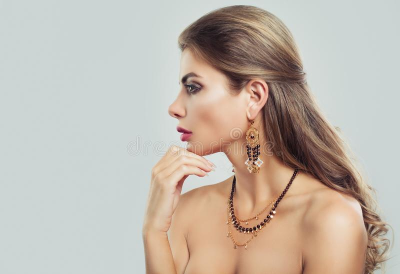 Nice Woman Fashion Model with Makeup, Wavy Brown Hair. And Jewelry Necklace on Gray Background royalty free stock photos