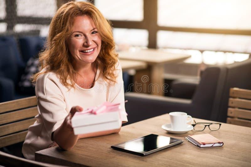 Nice woman giving a box stock photos