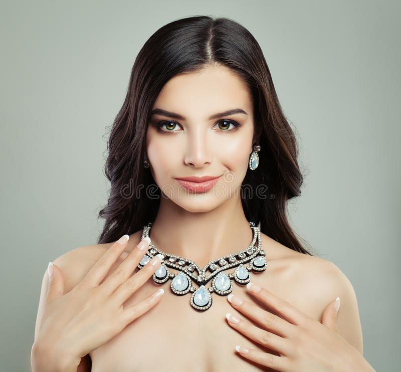Nice Woman with Healthy Hair, Makeup and Jewelry Necklace. On Gray Background stock photos