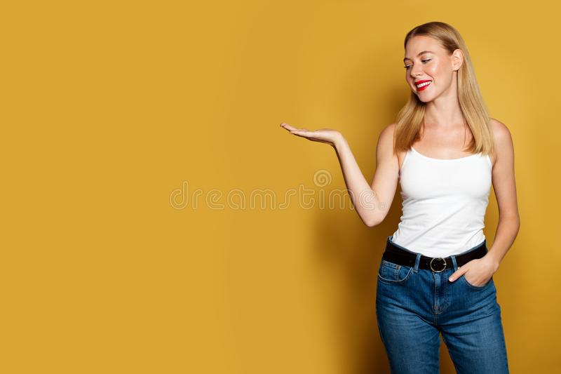 Nice woman looking at empty open hand on bright yellow background.  stock photos