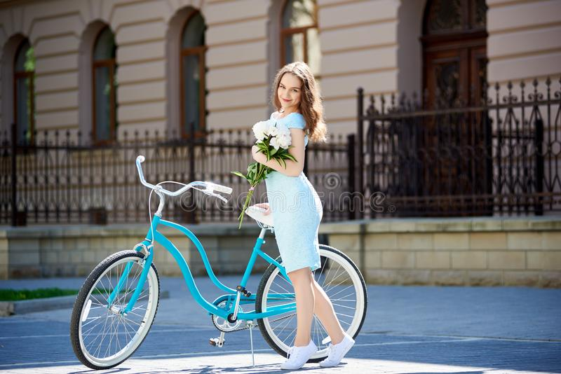Nice woman with peonies near blue retro bicycle in sunlight stock photos