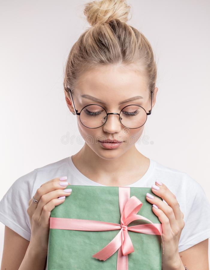A nice woman is sad to receive a modest gift from her boyfriend. Nice woman is sad to receive a modest gift from her boyfriend. undue expectation. New Year and royalty free stock photos