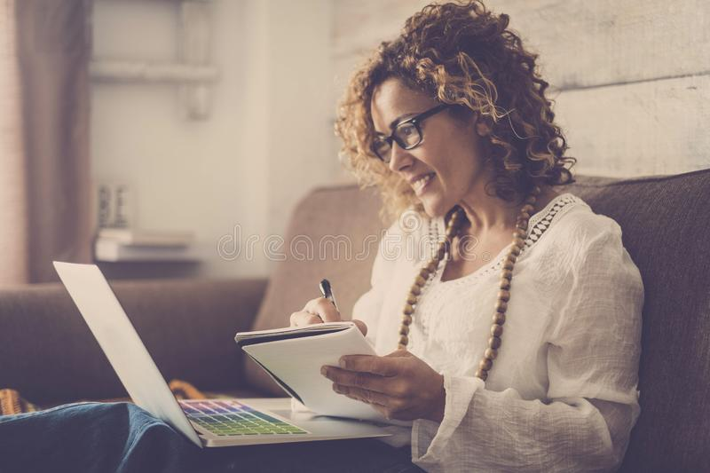 Nice woman type on a laptop working at home freedom and happy. taking notes on paper royalty free stock photography