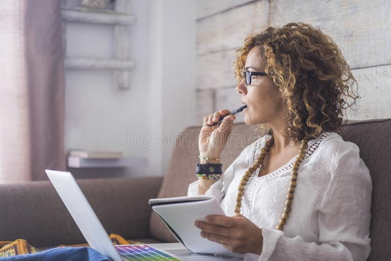 Nice woman type on a laptop working at home freedom and happy. thinking looking outside stock photos