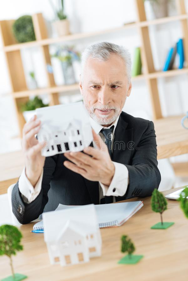 Satisfied real estate agent holding a good miniature of a real house. Nice work. Clever experienced worker of a real estate agency sitting in his office with a stock photo