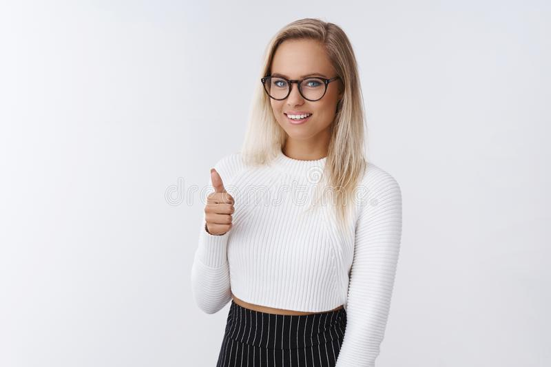 Nice work, proud of you. Pleased and delighted attractive elegant and flirty woman in glasses and skinny white sweater stock image