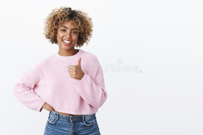 Nice, you did best. Portrait of happy cute and outgoing african american female model with blond haircut smiling. Joyfully and delighted showing thumb up stock photo