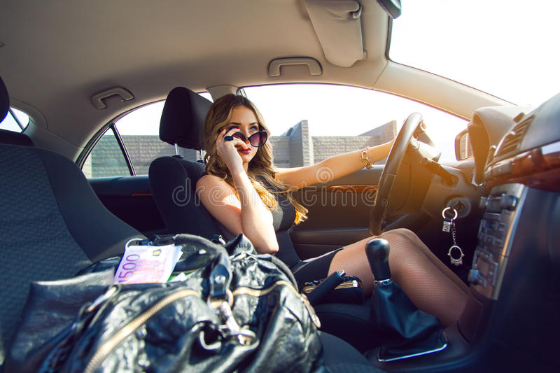 Nice young adult blonde girl with blue eyes driving car with bag stock images