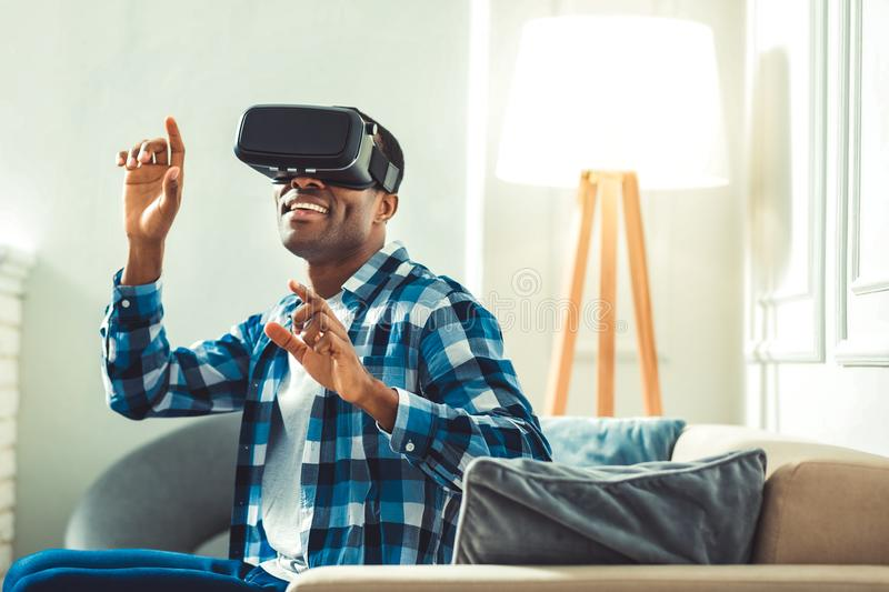 Nice young afro american man delating VR. Innovative possibilities. Cheerful afro american man putting on VR glasses and gesturing royalty free stock photography
