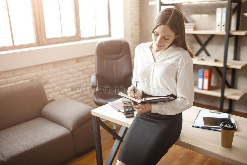 Nice young beautiful businesswoman lean to table in room. She look at tablet and smile. Calm peaceful human. royalty free stock photography