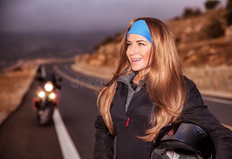 Nice young biker on the road royalty free stock photo