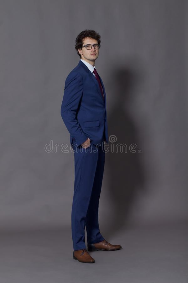 Young businessman standing with hands in his pockets stock image