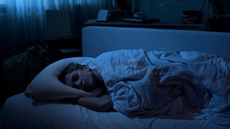 Nice young boy sleeping deep in his bed after hard day at university, relaxation royalty free stock image