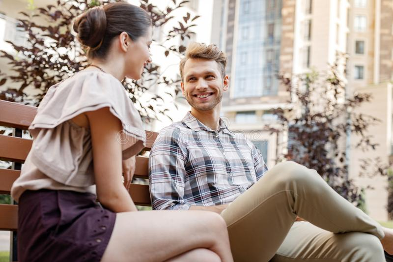 Nice young couple having a conversation. First date. Nice young couple sitting together on the bench while having a conversation royalty free stock photo