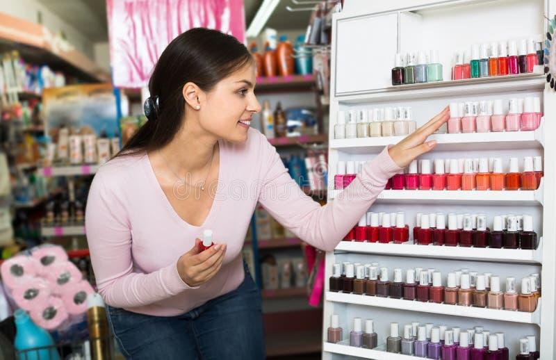 Nice young girl choosing nail polish royalty free stock images