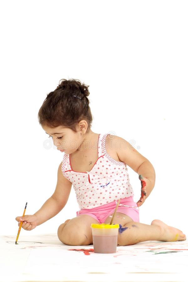 Nice young girl draws painting while sitting on the floor royalty free stock photography