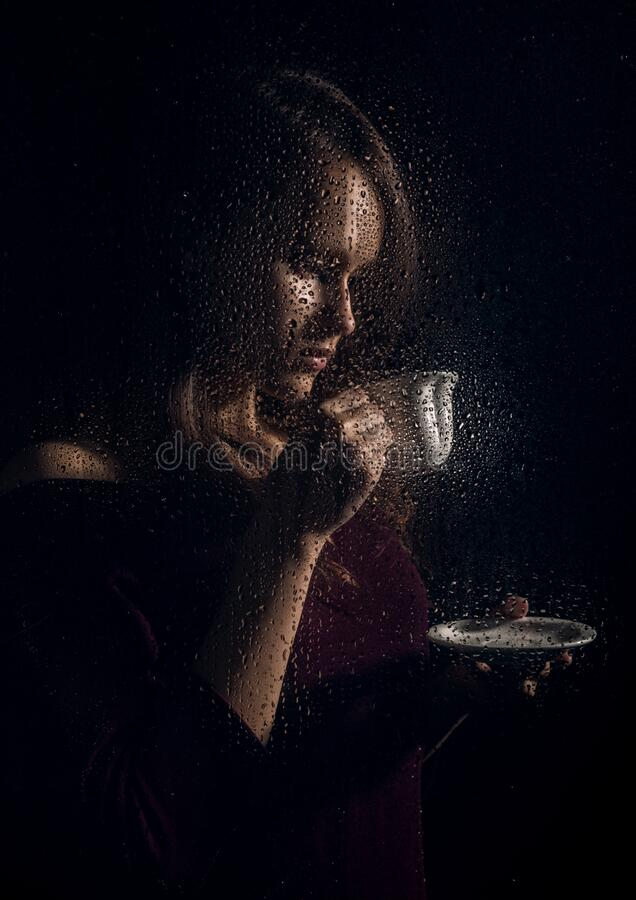 Nice young girl drinks coffee behind the wet glass, raindrops on glass stock images