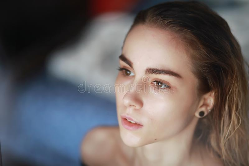 A nice young girl with wet hair. Behind the glassr royalty free stock photos