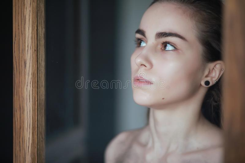 A nice young girl with wet hair. Behind the glassr royalty free stock images