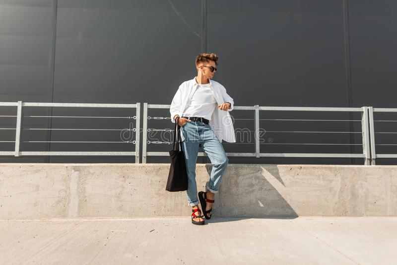 Nice young man hipster in a vintage shirt in blue jeans in red sandals in dark sunglasses with a fabric bag is resting. On the street near a gray building royalty free stock photos