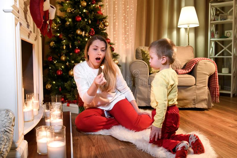 Nice young mommy blowing down a burning match stock image