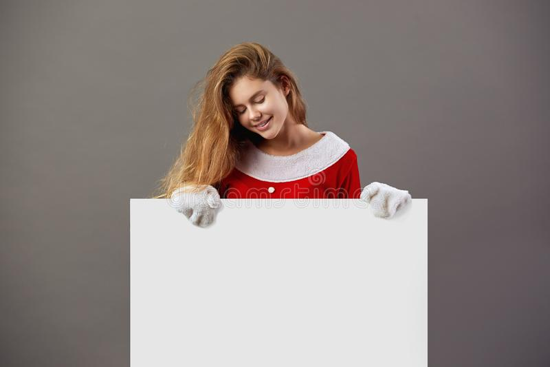 Nice young mrs.Santa Claus dressed in the red robe and white gloves holds the white canvas in front of her on the gray stock image