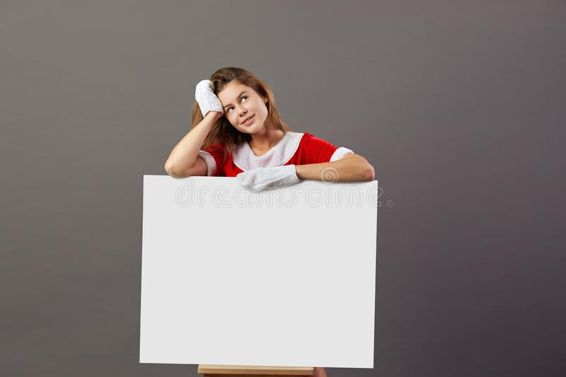 Nice young mrs.Santa Claus dressed in the red robe and white gloves stands behind a white canvas and leans on it on the stock photography