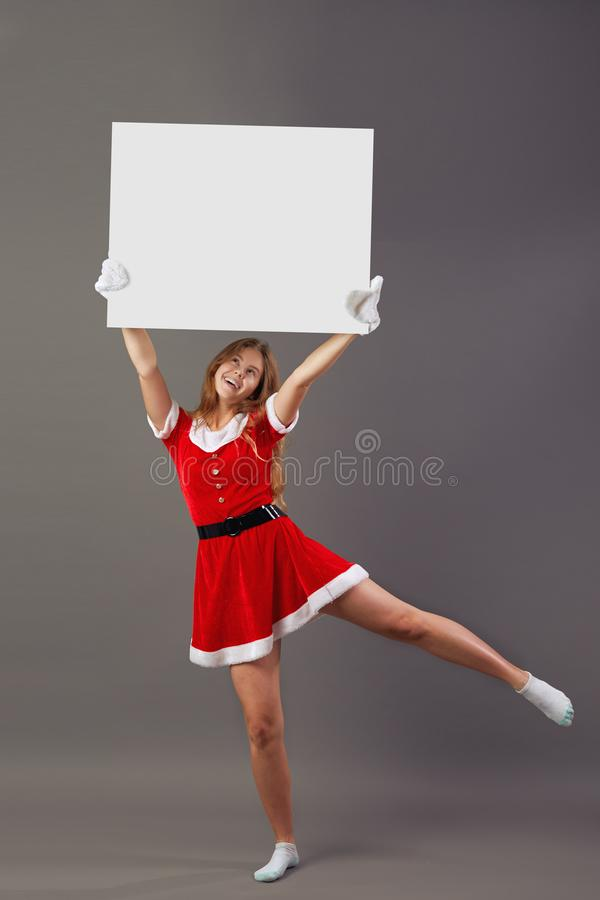 Nice young mrs.Santa Claus dressed in the red robe, white gloves and white socks holds the white canvas over her head on royalty free stock photography