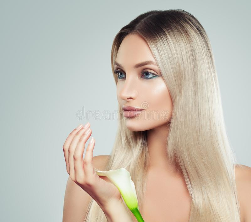 Nice Young Woman with Clean Fresh Skin, Healthy Blonde Hair. And White Lily Flowers in her Hand. Facial Treatment, Cosmetology, Beauty, Skin Care and Spa royalty free stock photography