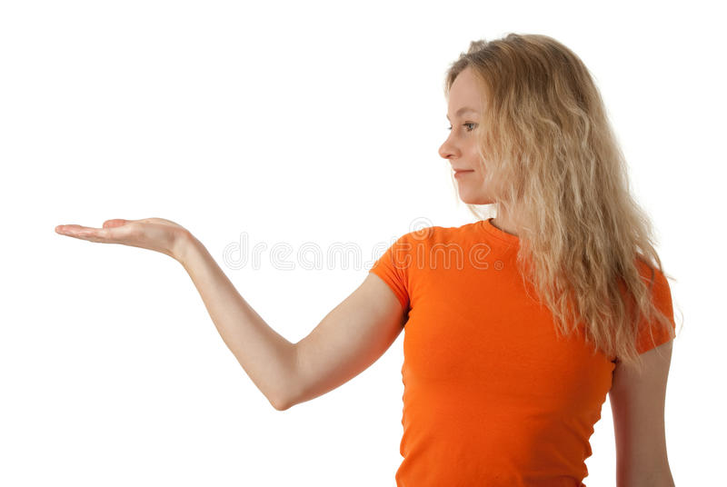 Nice young woman holding her hand palm up. Nice young woman in orange t-shirt holding her hand palm up, ready to hold your product royalty free stock photography