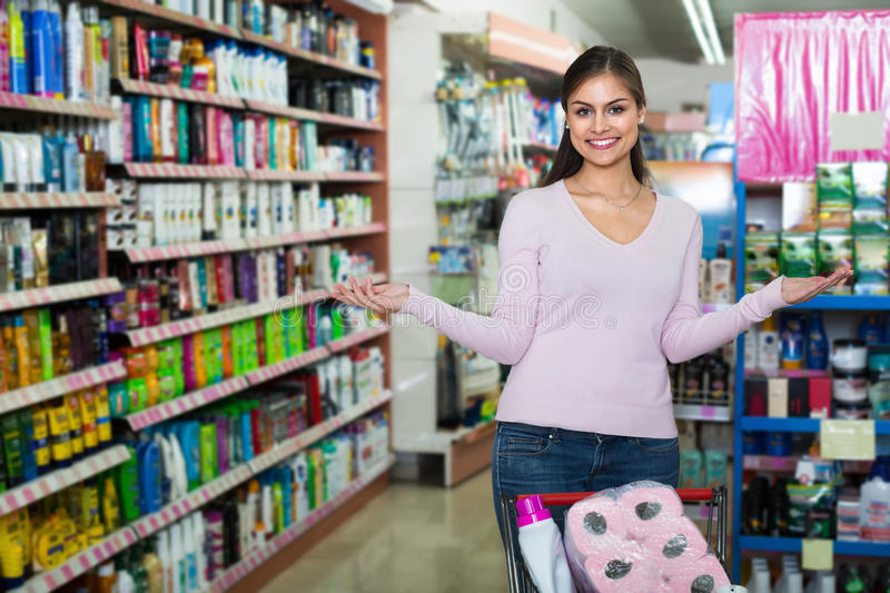 Nice young woman pushing shopping trolley royalty free stock photography
