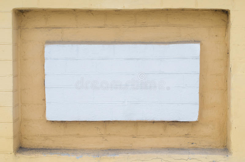 Niche in the brick wall painted in white and yellow stock photo