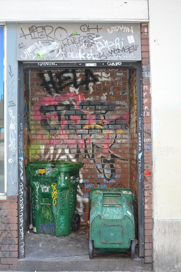 Grafitii and garbage cans in Portland, Oregon. This is a niche in a building painted with grafitii on SW Yamhill in Portland, Oregon used for storing garbage stock photos