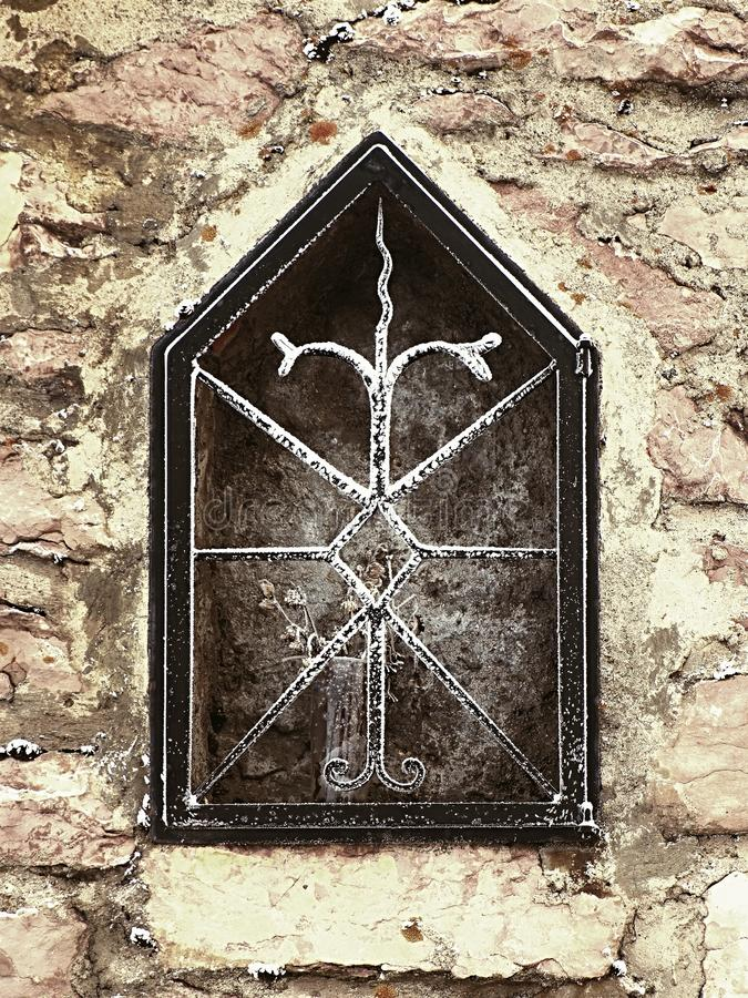 Niche in stony wall of village house with frozen flower. Forged corroded steel bars. Niche in stony wall of village house with frozen flower. Forged steel bars royalty free stock photography