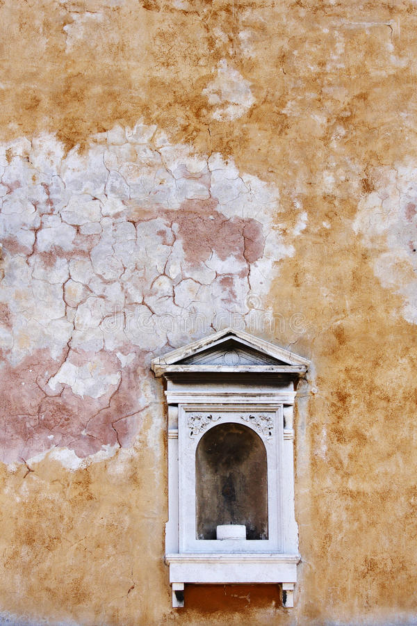 Niche in a weathered wall. An ornate niche in a weathered wall, Venice stock photos