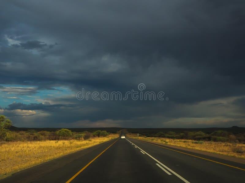 Nicht für den Straßenverkehr durch schwarze regnende Wolke auf Landstraßenautoreise durch getrocknetes Gras der Savanne fahrend A lizenzfreie stockfotos
