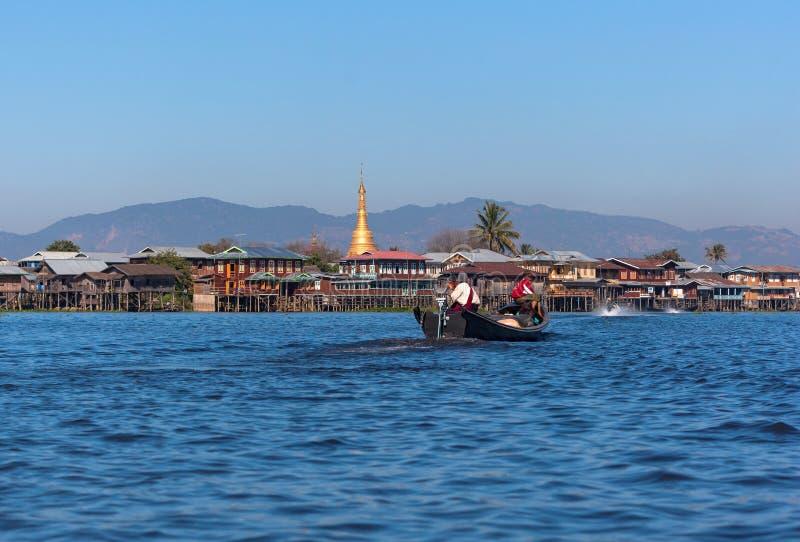 Nicht identifizierte Birmane sind ridind das Longtail-Boot, die Pagode und traditionellen Haushintergrund haben lizenzfreie stockfotos