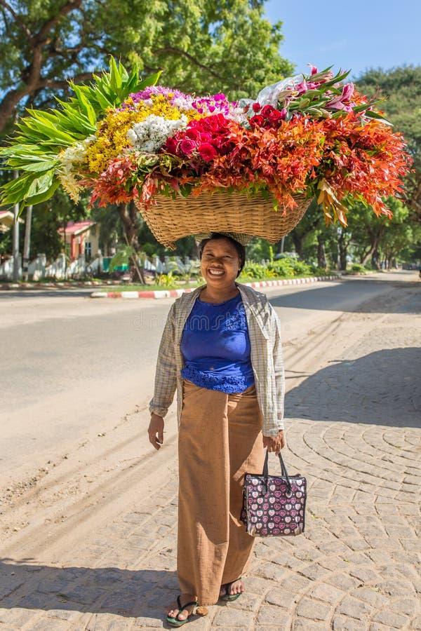 Nicht identifizierte birmanische Frau, die großen Korb von Blumen auf Straßen von Bagan, Myanmar trägt lizenzfreie stockfotografie