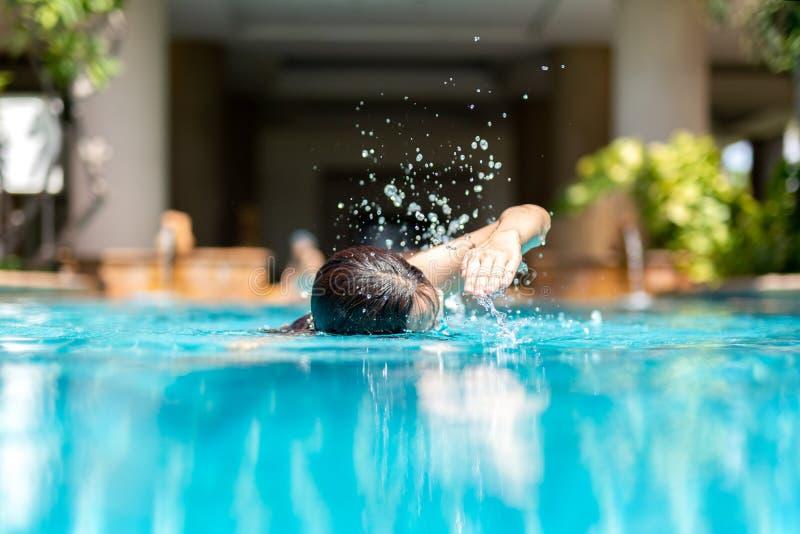 Nicht identifizierte Frau, die im Urlaub Schwimmen des vorderen Schleichens im Swimmingpool tut lizenzfreie stockfotos