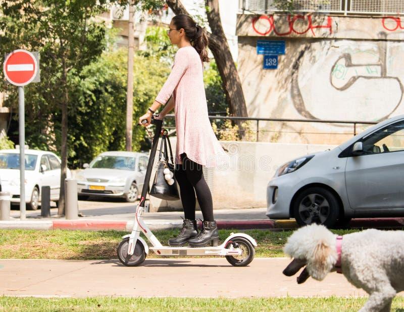 Nicht identifizierte Frauen, die einen elektrischen Roller reiten stockfotografie