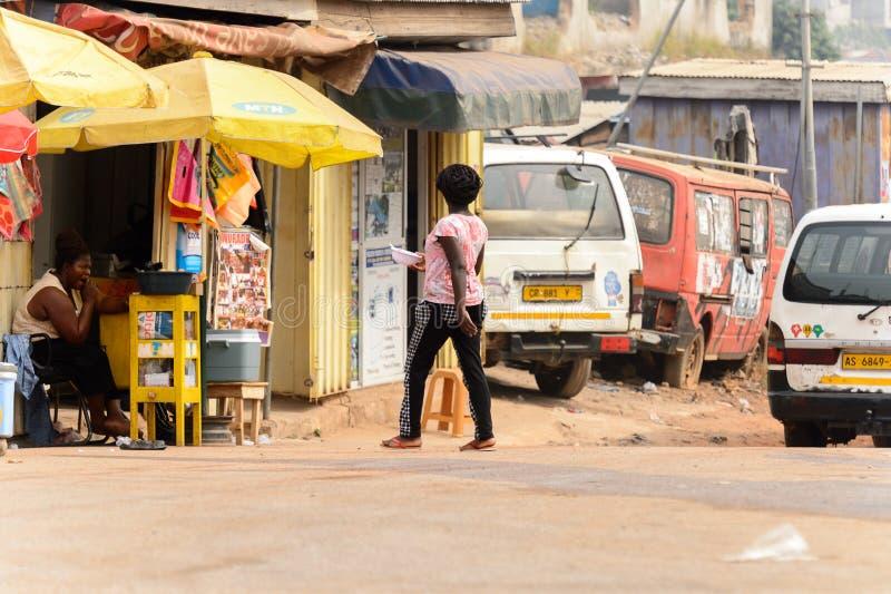Nicht identifizierte ghanaische Frau mit Borten von hinten Wege zum Th lizenzfreies stockbild