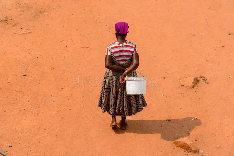 Nicht identifizierte ghanaische Frau von hinten Wege auf der Straße herein stockfotos