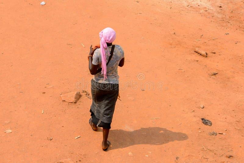 Nicht identifizierte ghanaische Frau von hinten Wege entlang der Straße herein lizenzfreie stockfotos